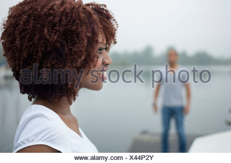 Portrait of young woman smiling with man in background - Stock Photo