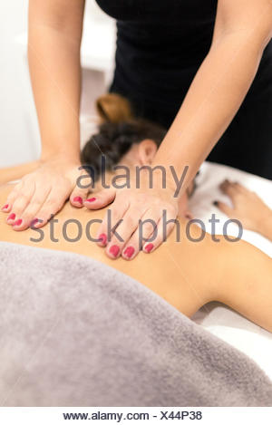 Young woman receiving a back massage - Stock Photo