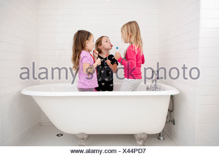 Three young girls standing in bath with lollipops - Stock Photo