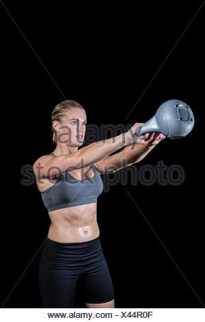 Muscular woman swinging heavy kettlebell - Stock Photo