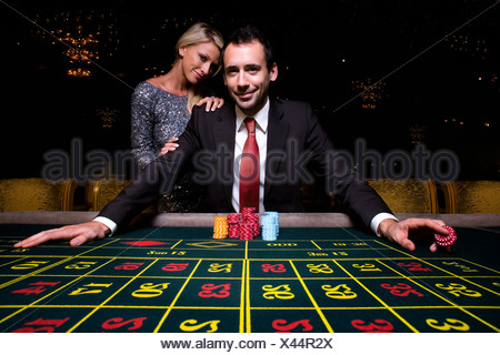Woman by man gambling at roulette table, portrait, low angle view - Stock Photo
