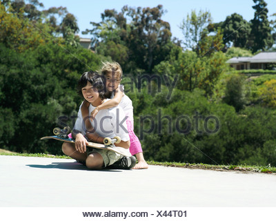 Girl 6 8 embracing brother in park boy 10 12 sitting with skateboard smiling portrait - Stock Photo