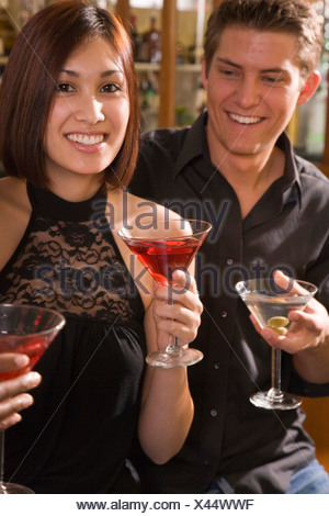 Happy young adult couple sitting at bar holding drinks - Stock Photo