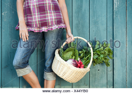 Germany, Bavaria, Woman leaning against barn door holding basket with fresh vegetables - Stock Photo
