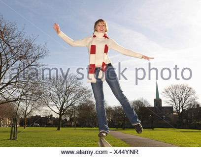 Woman balancing on bench in park - Stock Photo