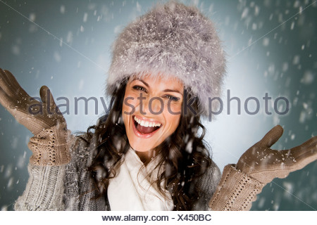 A young woman standing in the falling snow, smiling - Stock Photo