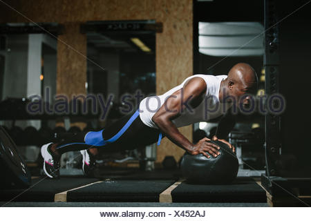 Physical athlete doing push-ups on medicine ball in gym - Stock Photo