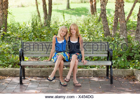 Two Girls legs crossed on a bench - Stock Photo