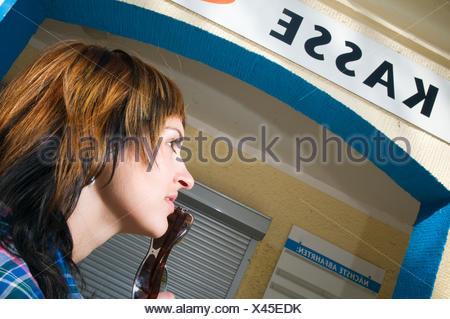 Kopf-und-Schulter-Aufnahme einer jungen brünetten Frau in Untersicht und einem Kassen-Schild im Hintergrund - Stock Photo