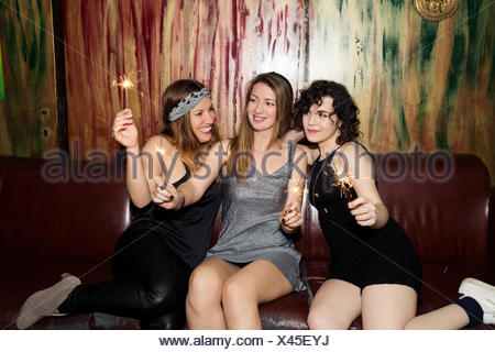 Three adult female friends playing with sparklers on night out in bar - Stock Photo