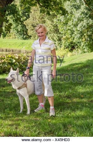 Woman with a dog on a walk in the park - Stock Photo