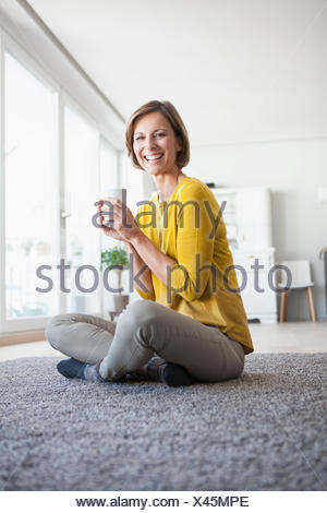 Relaxed woman at home sitting on floor holding cup - Stock Photo