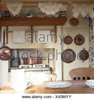 Vintage copper pans on wall beside range oven in cottage kitchen with lace mats hung on a wooden pulley - Stock Photo