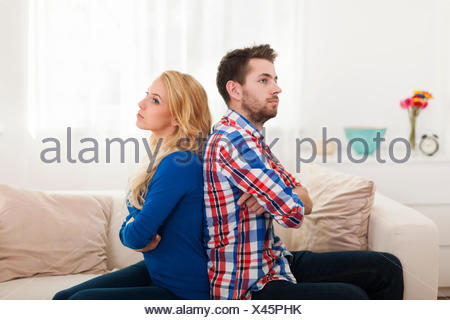 Angry young couple sitting back to back at home - Stock Photo