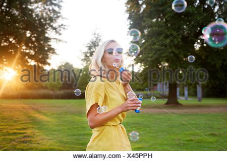 Portrait of young woman wearing yellow dress blowing bubbles in park at sunset - Stock Photo