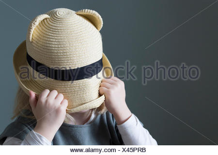 Girl pulling her hat down over her face - Stock Photo