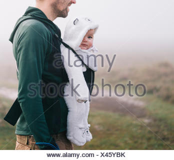 A man carrying a baby in a baby carrier on his chest, outdoors on a misty autumn day - Stock Photo