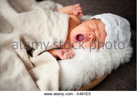 Portrait of newborn baby girl yawning - Stock Photo