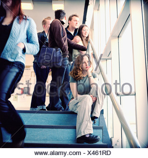 Lonely student with people in the backgound - Stock Photo