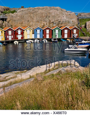 Boat houses in a row against cliffs with peaceful lake in foreground at Smogen, Sweden - Stock Photo
