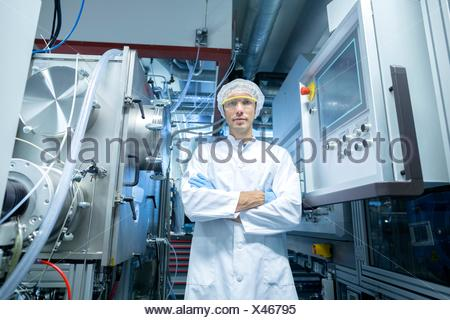 Portrait of male scientist with arms folded in lab cleanroom - Stock Photo