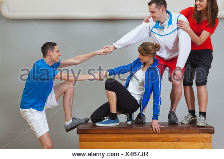 Germany, Berlin, Young men and women messing on vaulting horse - Stock Photo