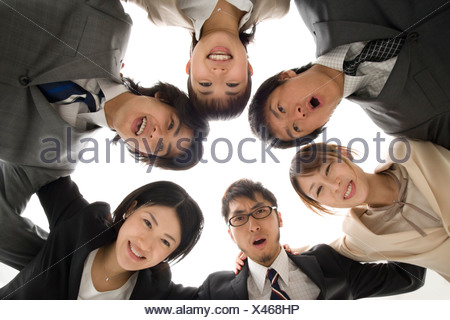 Business people huddled in circle - Stock Photo