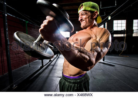 A crossfit athlete performs bicep curls. - Stock Photo