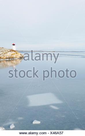 Sweden, Bohuslan, Orust, Mollosund, Lighthouse by frozen sea - Stock Photo