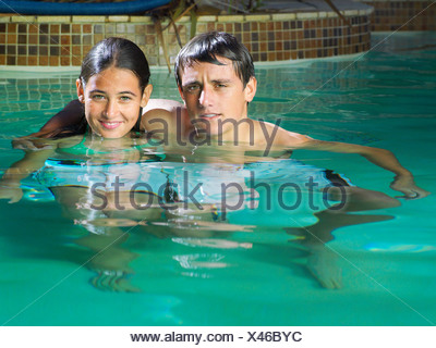 Teenage couple 15 17 relaxing in swimming pool boy with arm around girl smiling portrait - Stock Photo