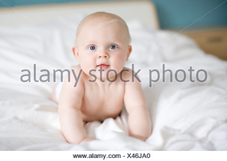 Portrait of a baby lying in a bed, Sweden. - Stock Photo