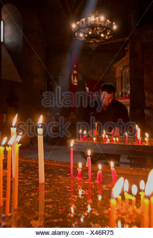 Worshiper inside the large chapel of St. Astvatsatsin, in the Khor virap monastery - Stock Photo