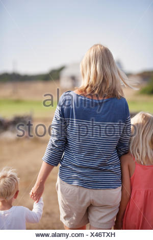 Sweden, Gotland, Faro, Mother with son (2-3) and daughter (10-11) holding hands - Stock Photo