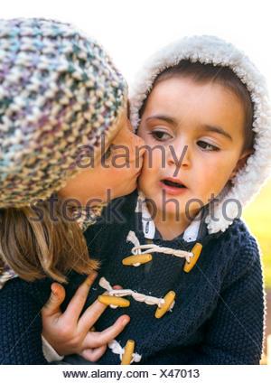 Girl kissing little boy - Stock Photo