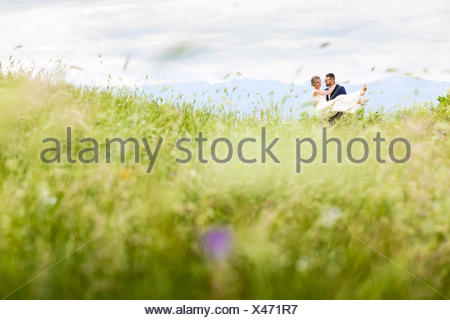 Groom carrying bride on meadow - Stock Photo