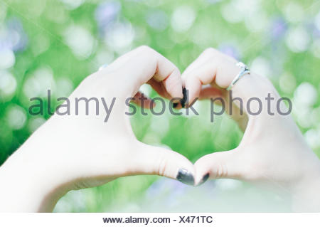 Woman making heart shape with hands - Stock Photo