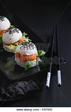 Mini rice sushi burgers with smoked salmon, green salad and sauces, black sesame served on black square plate with chopsticks and textile napkin over  - Stock Photo