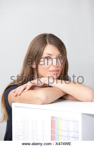 Portrait of woman in office leaning on cabinet - Stock Photo