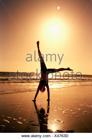 A woman doing a cartwheel on a beach at sunset - Stock Photo