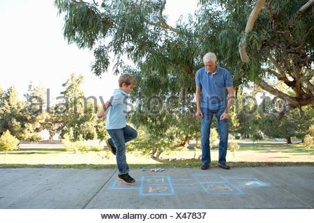 Boy on hopscotch, grandfather watching - Stock Photo