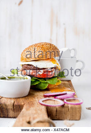 Fresh homemade burger with beef cutlet, egg, prosciutto and vegetables on wooden serving board with onion rings and pesto sauce - Stock Photo