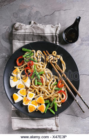 Cooking stir fry udon noodles, green beans, sliced paprika, boiled eggs, soy sauce with sesame seeds in black plate with wood chopsticks over gray tex - Stock Photo