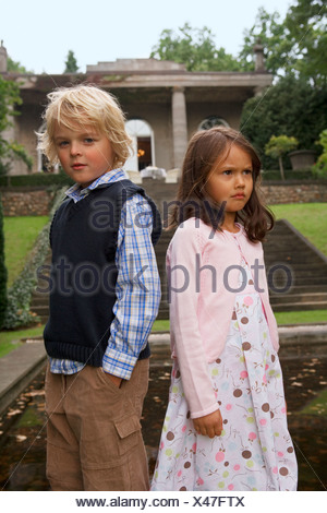 Close-up of a boy standing back to back with a girl - Stock Photo