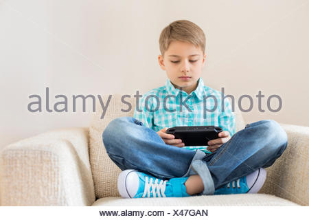 Boy playing hand-held video game on sofa - Stock Photo