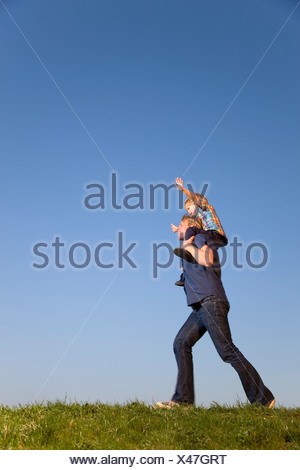 boy sitting on father's shoulders - Stock Photo