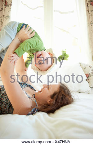 Sweden, Teenage girl (16-17) playing with sister (2-3) - Stock Photo