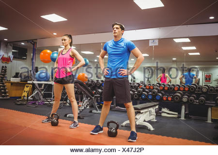Fit couple working out in weights room - Stock Photo