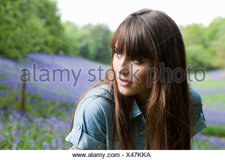 Young woman in field of bluebells - Stock Photo