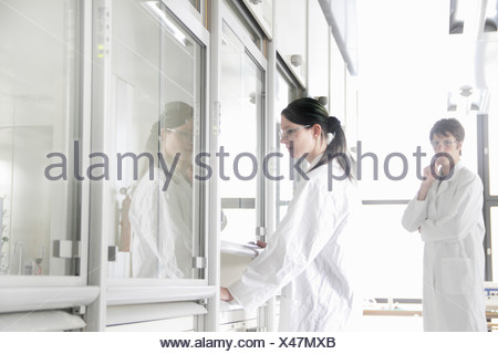 Chemistry students by fume cupboard in lab - Stock Photo