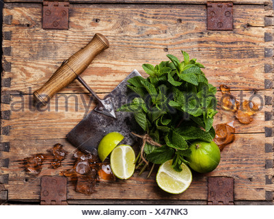 Ingredients for making mojitos Ice cubes, mint leaves and lime on wooden background - Stock Photo